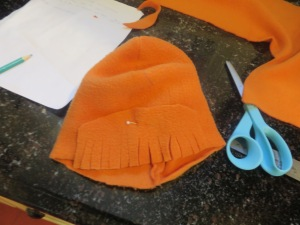 First row of bangs pinned to hat and ready to be sewn.