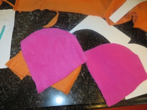 Two bonnet pieces cut from pink fleece.