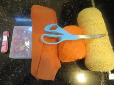 Two pieces (to size of your child's head*), matching yarn, yellow yarn, Wonder Clips, measuring tape, scissors.